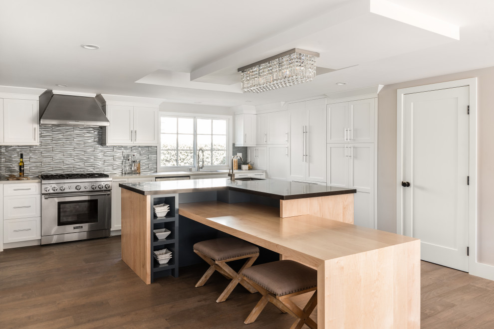 Example of a large transitional l-shaped brown floor kitchen design in Los Angeles with an undermount sink, shaker cabinets, white cabinets, gray backsplash, stainless steel appliances, an island and brown countertops