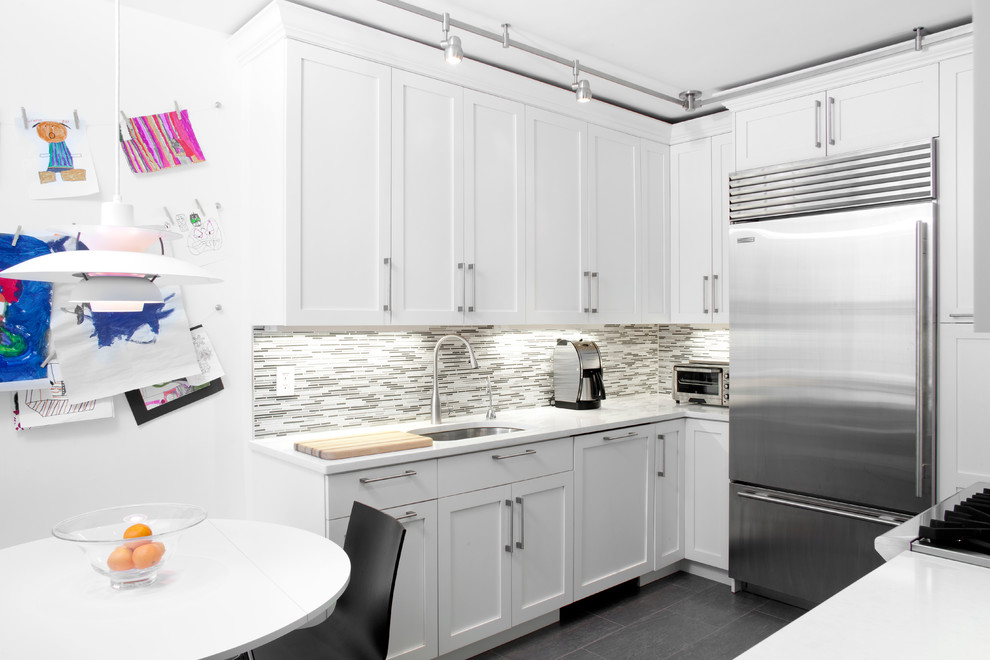 Trendy u-shaped eat-in kitchen photo in New York with an undermount sink, shaker cabinets, white cabinets, gray backsplash, matchstick tile backsplash and stainless steel appliances