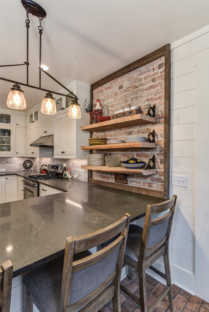 Kitchen - farmhouse u-shaped brick floor kitchen idea in Other with a farmhouse sink, shaker cabinets, white cabinets, beige backsplash, brick backsplash, stainless steel appliances, a peninsula and quartz countertops