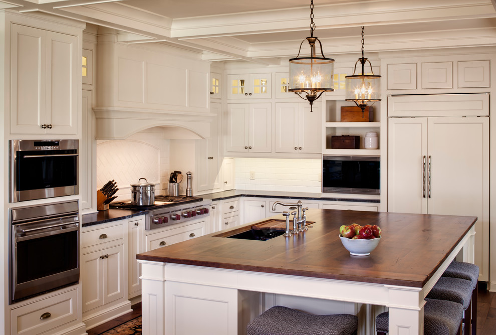 Example of a farmhouse kitchen design in Milwaukee with an undermount sink, beaded inset cabinets, white cabinets, wood countertops, white backsplash, subway tile backsplash and paneled appliances