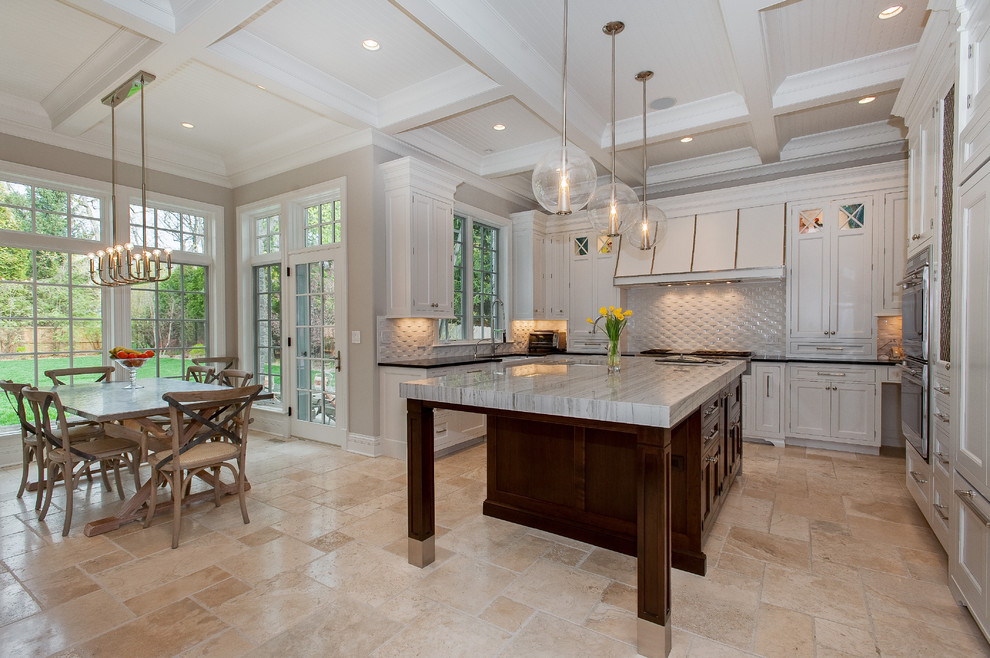 Example of a large trendy u-shaped limestone floor and beige floor eat-in kitchen design in Chicago with shaker cabinets, white cabinets, solid surface countertops, white backsplash, ceramic backsplash and an island