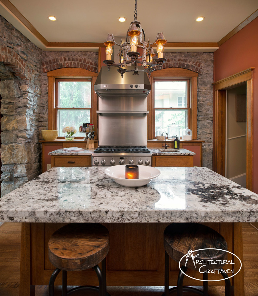Kitchen - rustic kitchen idea in Kansas City with a farmhouse sink, shaker cabinets, medium tone wood cabinets, granite countertops and paneled appliances
