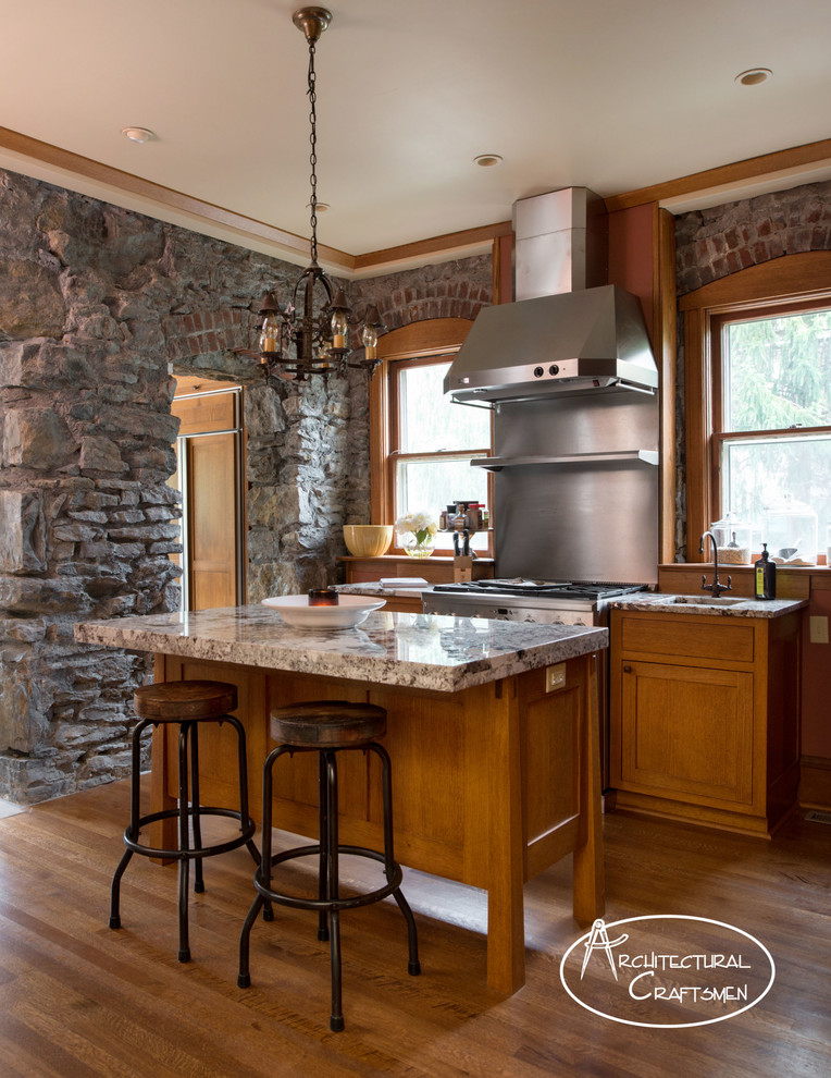 Example of a mountain style kitchen design in Kansas City with a farmhouse sink, shaker cabinets, medium tone wood cabinets, granite countertops and paneled appliances
