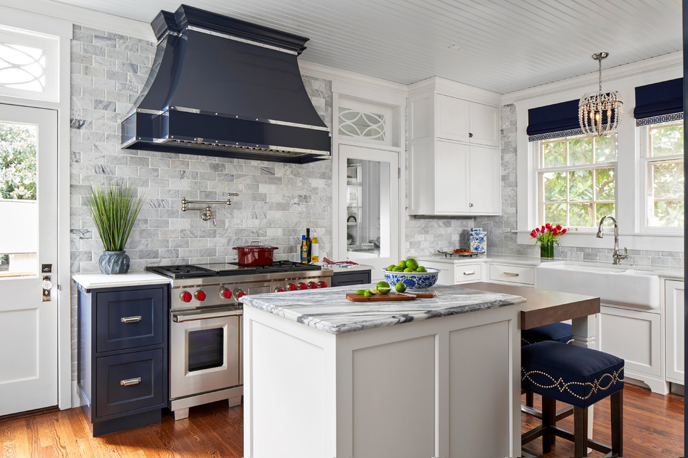 Example of a mid-sized classic u-shaped medium tone wood floor and brown floor enclosed kitchen design in Austin with a farmhouse sink, white cabinets, soapstone countertops, marble backsplash, an island, white countertops, gray backsplash, stainless steel appliances and shaker cabinets