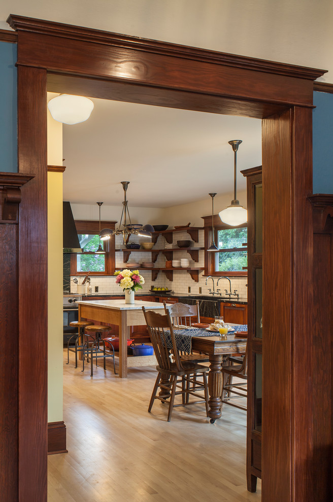 Inspiration for a huge craftsman l-shaped light wood floor eat-in kitchen remodel in Portland with an integrated sink, raised-panel cabinets, medium tone wood cabinets, soapstone countertops, white backsplash, subway tile backsplash, black appliances and an island