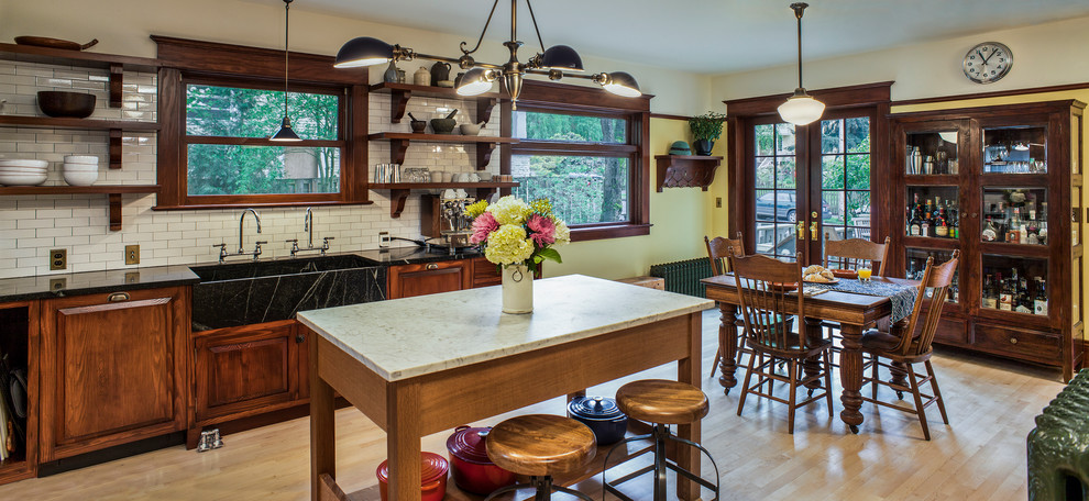 Eat-in kitchen - huge craftsman l-shaped light wood floor eat-in kitchen idea in Portland with an integrated sink, raised-panel cabinets, medium tone wood cabinets, soapstone countertops, white backsplash, subway tile backsplash, black appliances and an island