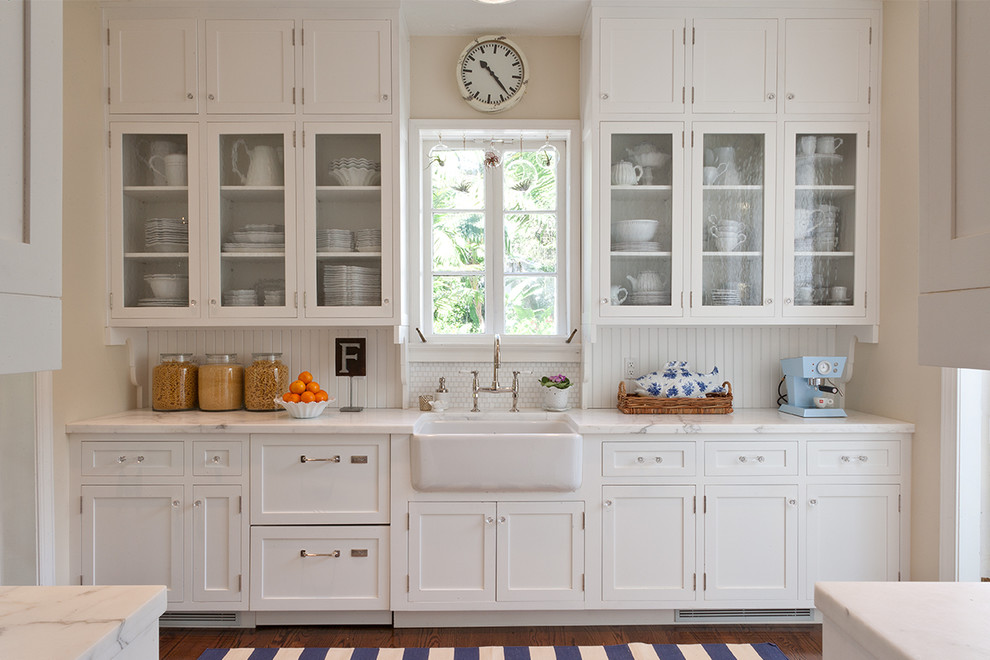 Mid-sized elegant galley dark wood floor enclosed kitchen photo in Miami with a farmhouse sink, glass-front cabinets, white cabinets, marble countertops, white backsplash, paneled appliances and no island