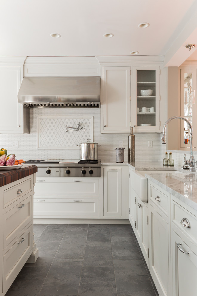 Elegant slate floor and gray floor kitchen photo in Boston with a farmhouse sink, recessed-panel cabinets, white cabinets, white backsplash and stainless steel appliances