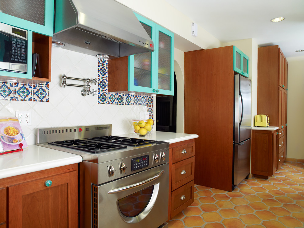 Example of a tuscan kitchen design in Los Angeles with stainless steel appliances, glass-front cabinets, blue cabinets, multicolored backsplash and quartz countertops