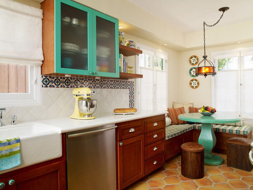 Inspiration for a mediterranean eat-in kitchen remodel in Los Angeles with glass-front cabinets, a farmhouse sink, blue cabinets, stainless steel appliances and quartz countertops