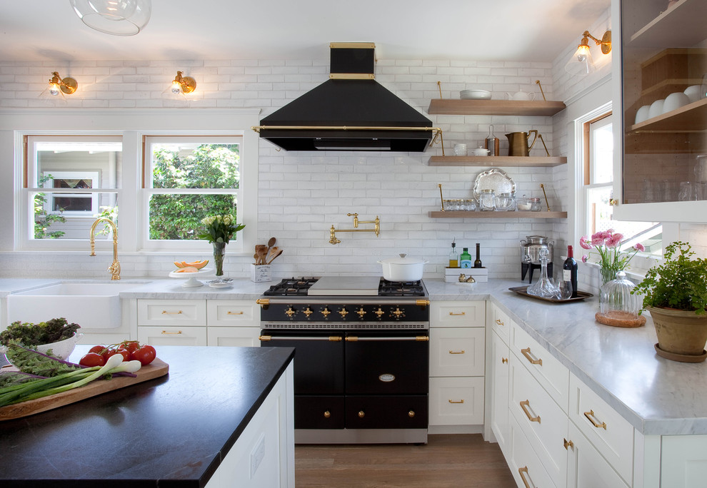 Transitional u-shaped medium tone wood floor kitchen photo in San Diego with a farmhouse sink, shaker cabinets, white cabinets, white backsplash, black appliances and an island