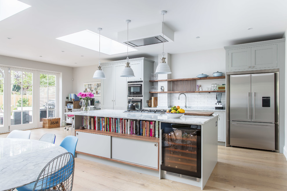 Trendy light wood floor eat-in kitchen photo in London with shaker cabinets, gray cabinets, marble countertops, white backsplash, stainless steel appliances, an island and subway tile backsplash