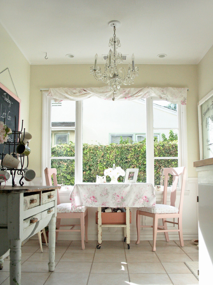 Example of a small cottage chic l-shaped ceramic tile eat-in kitchen design in Santa Barbara with a farmhouse sink, glass-front cabinets, white cabinets, wood countertops, white backsplash, stainless steel appliances and no island