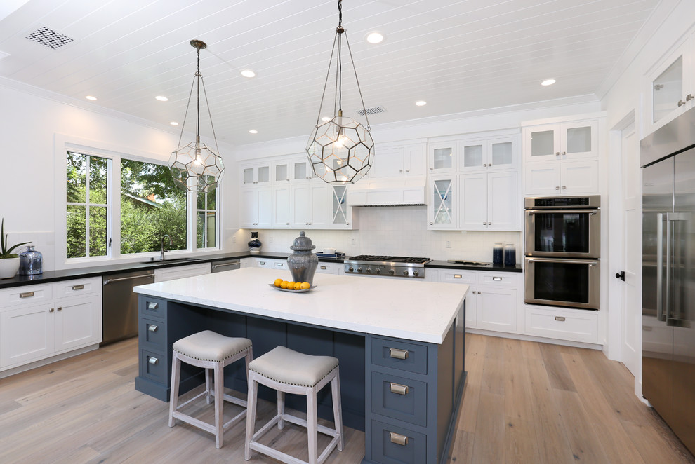 Inspiration for a transitional u-shaped medium tone wood floor kitchen remodel in Orange County with an undermount sink, white backsplash, subway tile backsplash, stainless steel appliances, an island, white cabinets and shaker cabinets