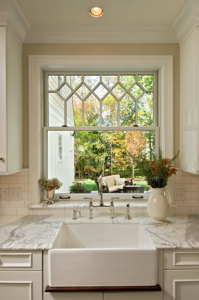 Ornate kitchen photo in New York with subway tile backsplash, a farmhouse sink, marble countertops, recessed-panel cabinets, white cabinets and white backsplash