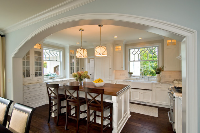 Example of a classic kitchen design in New York with glass-front cabinets, a farmhouse sink and wood countertops
