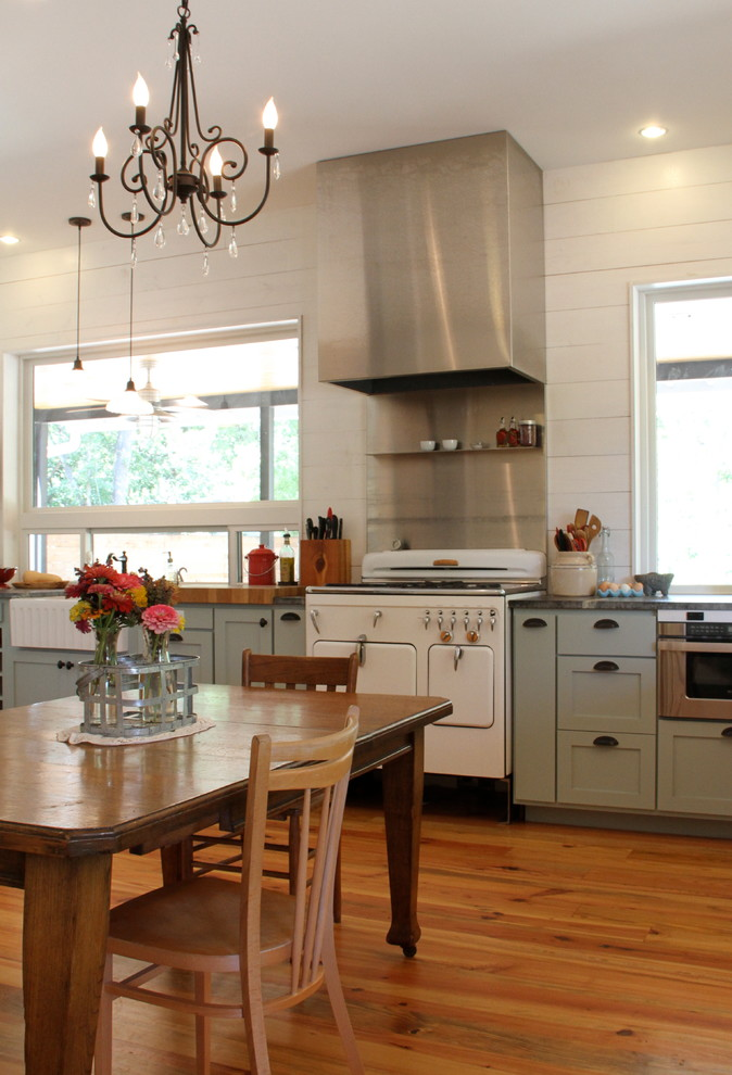 Eat-in kitchen - mid-sized cottage l-shaped medium tone wood floor eat-in kitchen idea in Austin with white appliances, blue cabinets, shaker cabinets, soapstone countertops, no island, white backsplash and a farmhouse sink