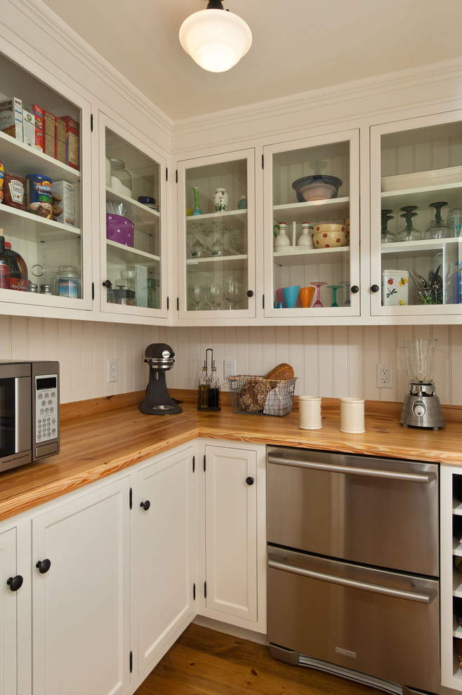 Inspiration for a timeless kitchen remodel in New York with wood countertops, glass-front cabinets, white cabinets and stainless steel appliances