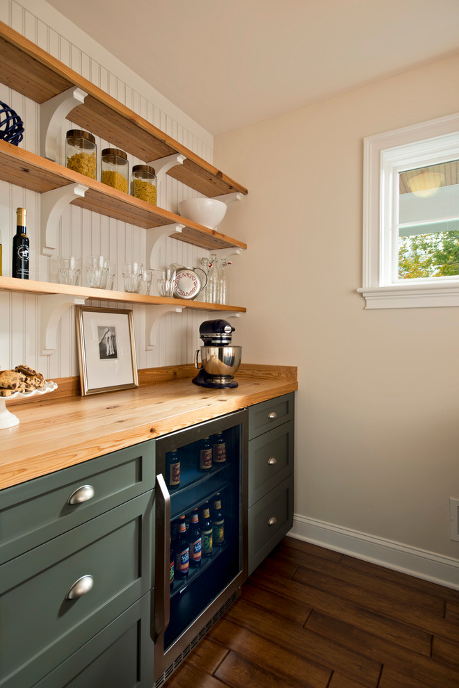 Elegant kitchen photo in New York with shaker cabinets, green cabinets, wood countertops and stainless steel appliances