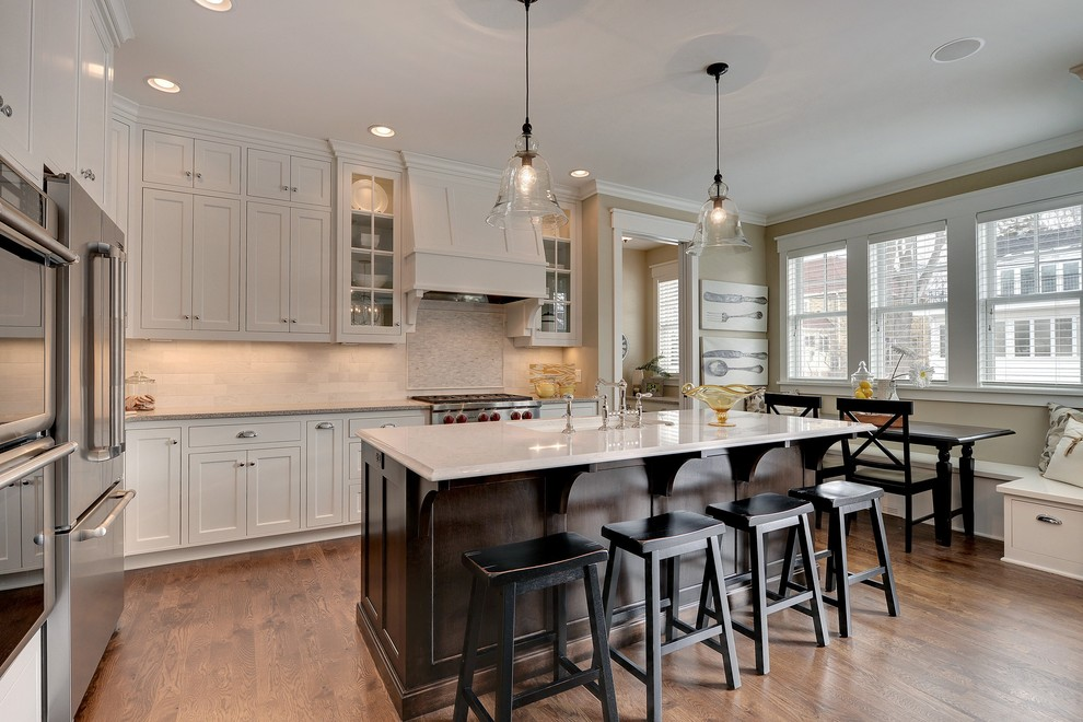Example of a classic eat-in kitchen design in Minneapolis with stainless steel appliances and stone tile backsplash
