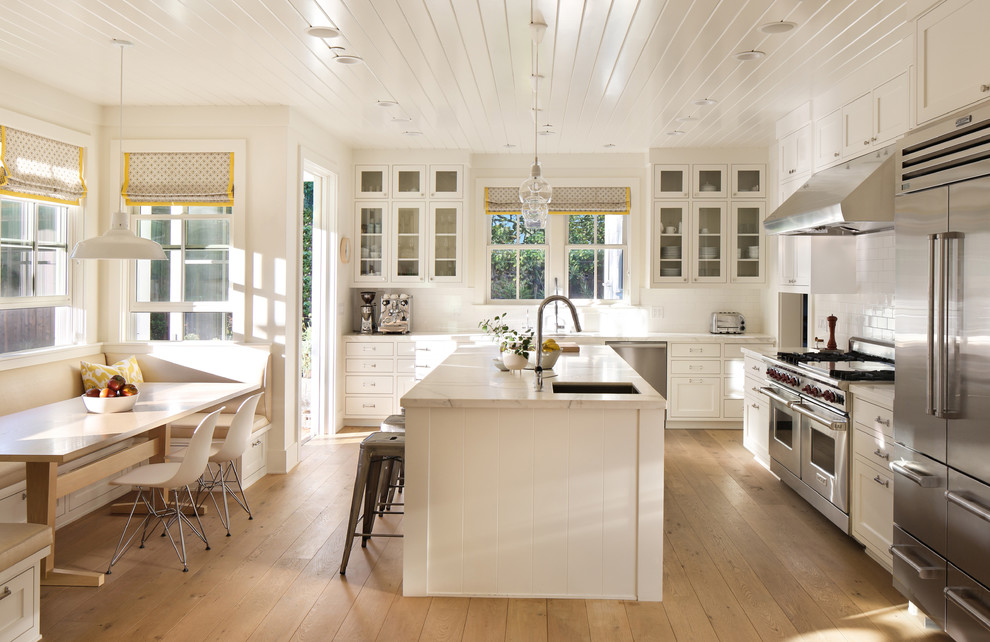 Example of a classic l-shaped medium tone wood floor eat-in kitchen design in San Francisco with an undermount sink, shaker cabinets, white cabinets, white backsplash, subway tile backsplash, stainless steel appliances and an island