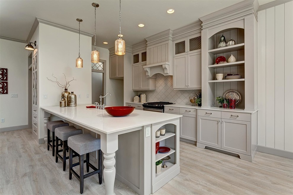 Open concept kitchen - mid-sized traditional single-wall light wood floor open concept kitchen idea in Boise with shaker cabinets, beige cabinets, quartz countertops, beige backsplash, stainless steel appliances and a peninsula