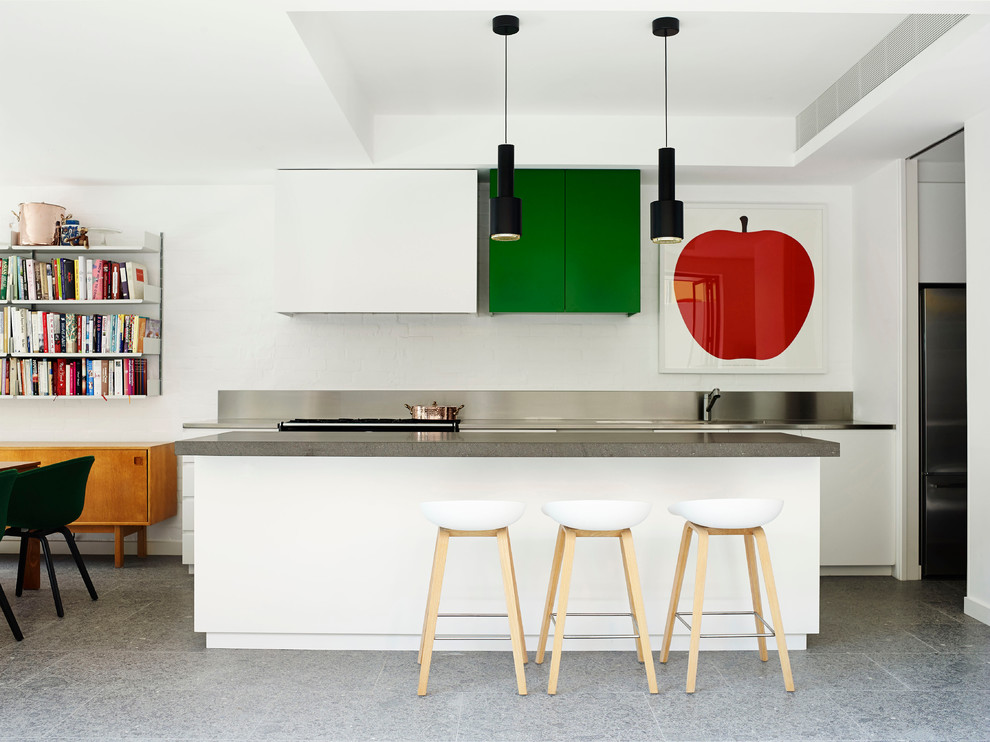 Example of a mid-sized trendy galley eat-in kitchen design in Sydney with flat-panel cabinets, white cabinets, an island and stainless steel countertops