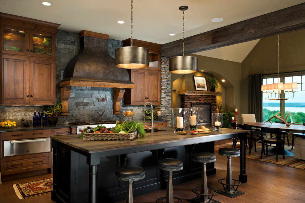 Example of a mountain style dark wood floor eat-in kitchen design in New York with raised-panel cabinets, dark wood cabinets, black backsplash, stainless steel appliances, an island and slate backsplash