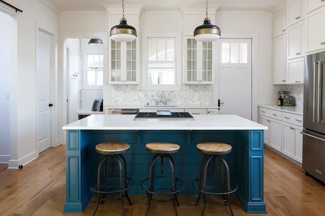 Idéer för ett mellanstort klassiskt parallellkök, med en undermonterad diskho, vita skåp, rostfria vitvaror, ljust trägolv, en köksö och luckor med infälld panel
