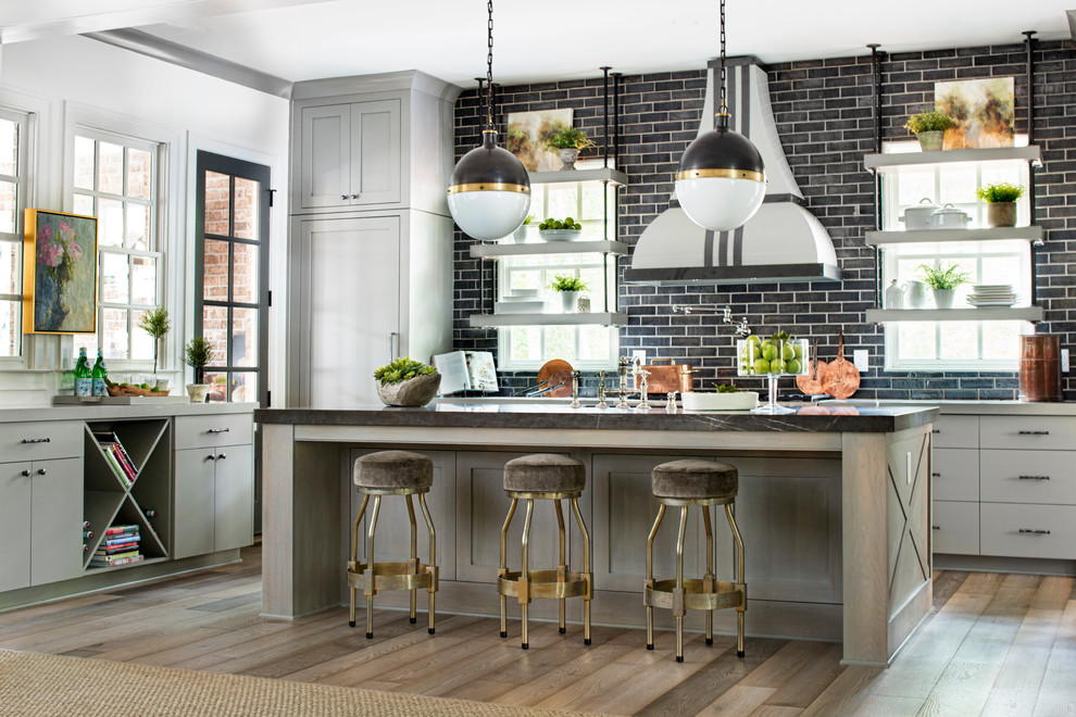 Inspiration for a transitional u-shaped medium tone wood floor kitchen remodel in Atlanta with quartz countertops, an island, flat-panel cabinets, gray cabinets and black backsplash