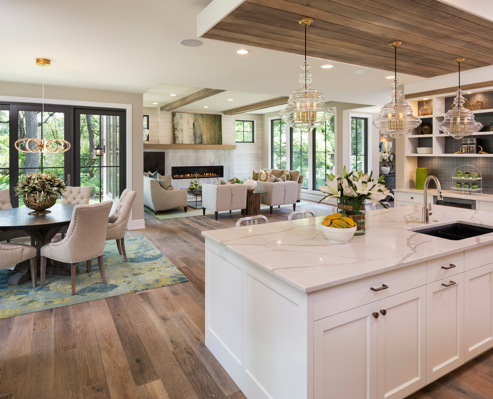 Transitional light wood floor open concept kitchen photo in Minneapolis with an undermount sink, shaker cabinets, white cabinets, black backsplash and an island