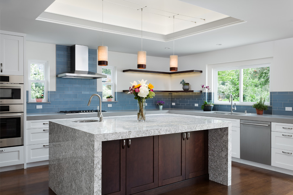 Example of a transitional l-shaped dark wood floor and brown floor kitchen design in San Francisco with a double-bowl sink, shaker cabinets, white cabinets, blue backsplash, glass tile backsplash, stainless steel appliances and an island