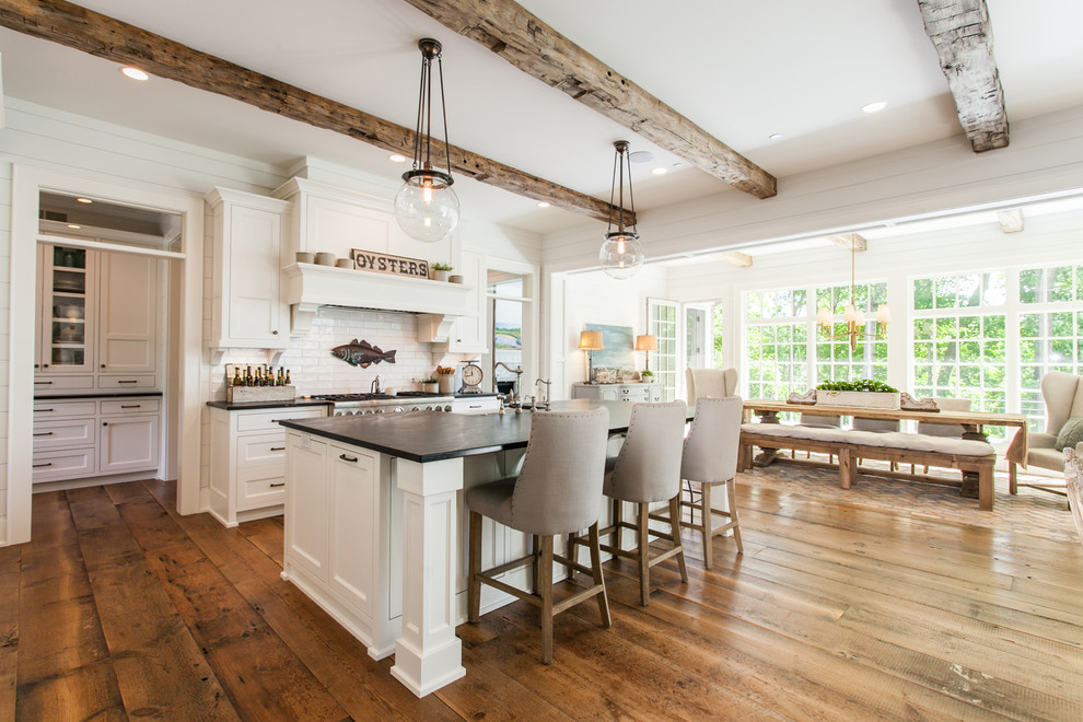Design ideas for a rural galley open plan kitchen with white cabinets, granite worktops, white splashback, stainless steel appliances, medium hardwood flooring, an island, brown floors, shaker cabinets, metro tiled splashback and black worktops.