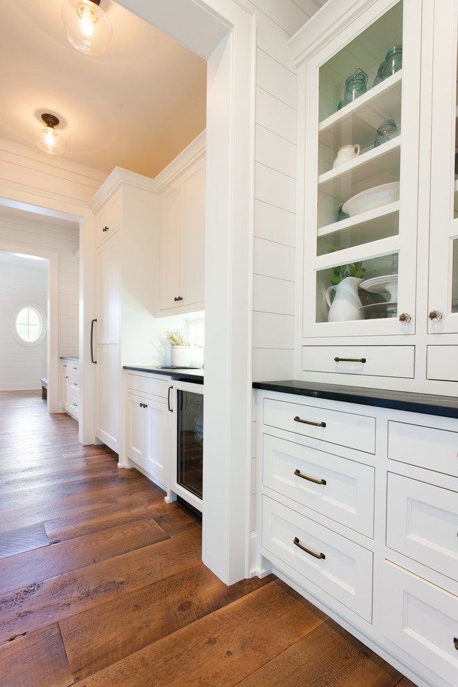 Example of an eclectic galley medium tone wood floor and brown floor kitchen pantry design with a drop-in sink, white cabinets, granite countertops and white backsplash