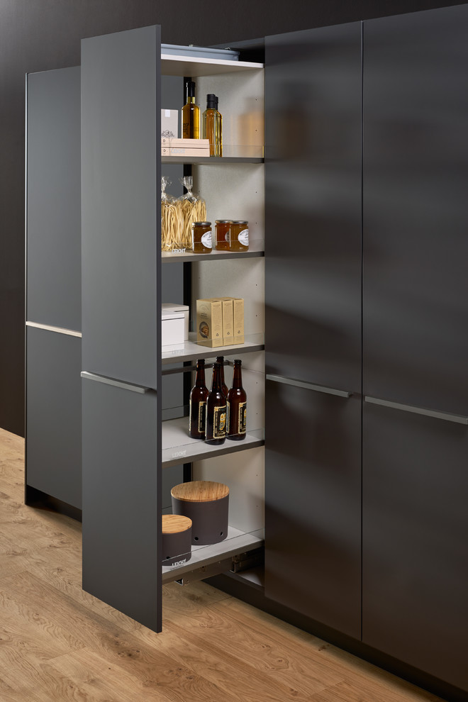 Example of a large minimalist single-wall concrete floor kitchen pantry design in New York with a double-bowl sink, flat-panel cabinets, gray cabinets, solid surface countertops, brown backsplash, stainless steel appliances and an island