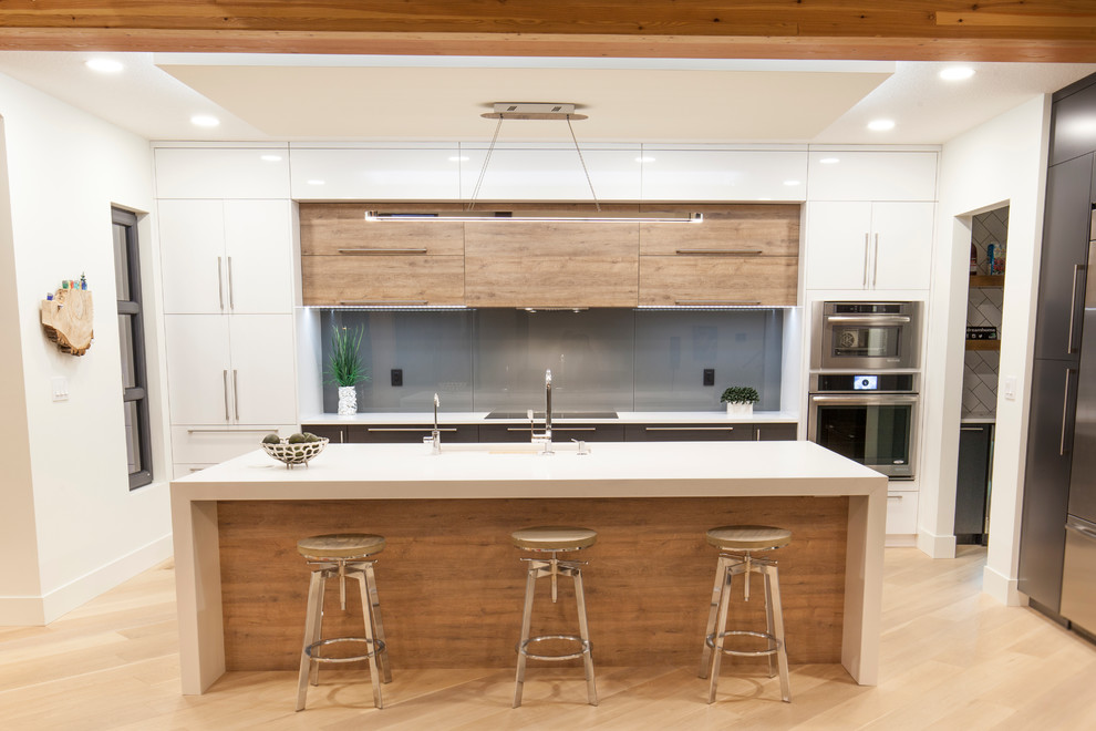 Large trendy galley light wood floor eat-in kitchen photo in Edmonton with an undermount sink, flat-panel cabinets, white cabinets, solid surface countertops, gray backsplash, glass sheet backsplash, stainless steel appliances and an island
