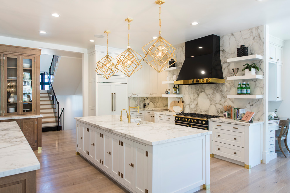 Example of a large trendy l-shaped medium tone wood floor and brown floor eat-in kitchen design in Salt Lake City with a farmhouse sink, shaker cabinets, white cabinets, marble countertops, white backsplash, marble backsplash, paneled appliances and two islands