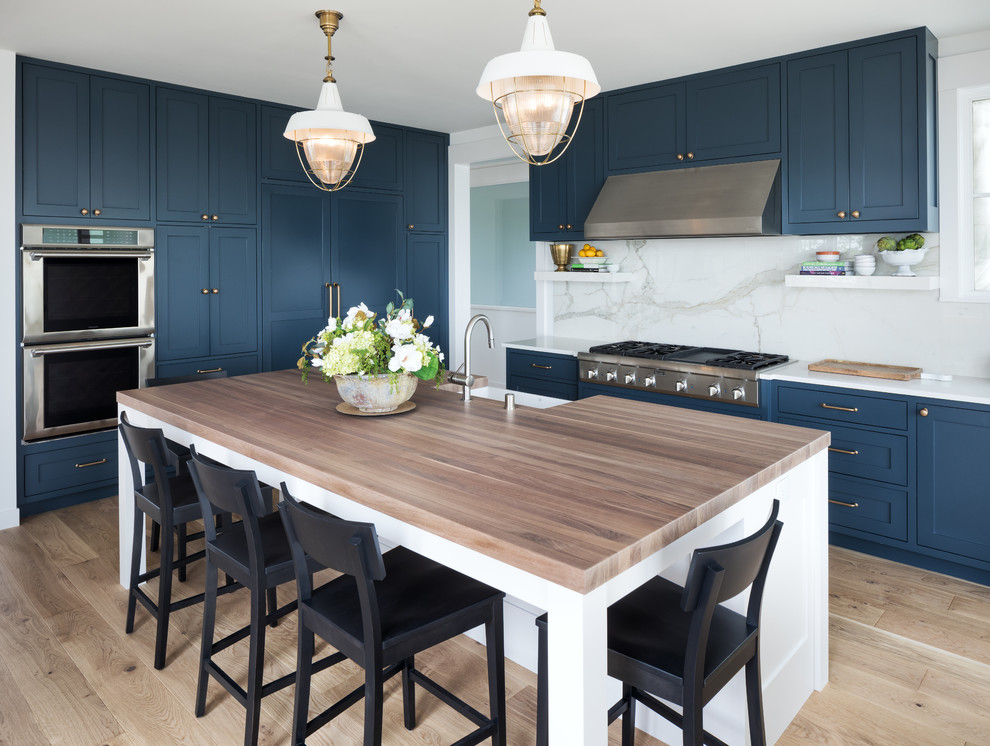 Inspiration for a coastal light wood floor and beige floor kitchen remodel in Minneapolis with a farmhouse sink, shaker cabinets, blue cabinets, white backsplash, marble backsplash, stainless steel appliances, an island and white countertops