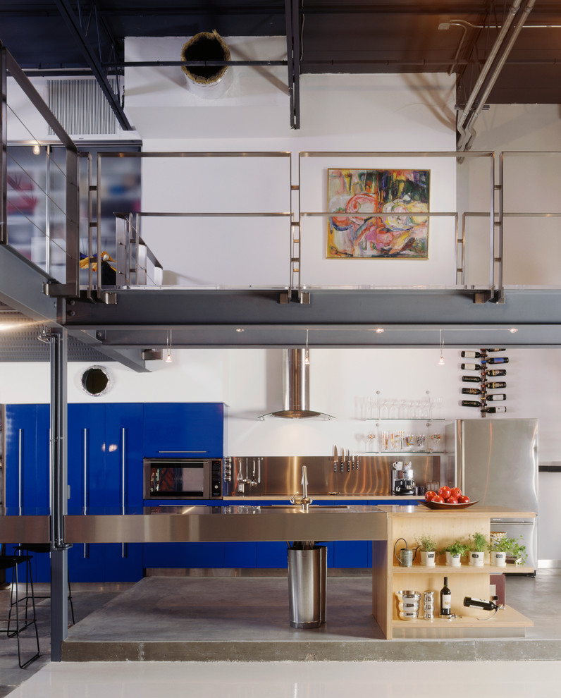 Kitchen - industrial kitchen idea in Tampa with stainless steel appliances and stainless steel countertops