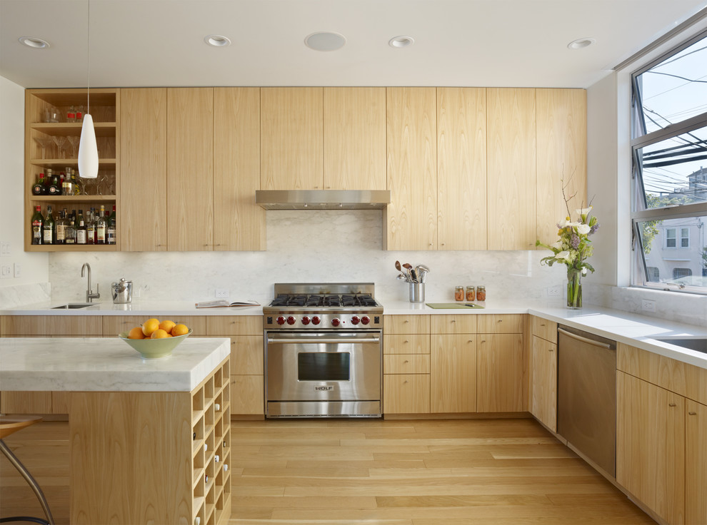 Example of a trendy kitchen design in San Francisco with flat-panel cabinets, light wood cabinets, white backsplash and stainless steel appliances