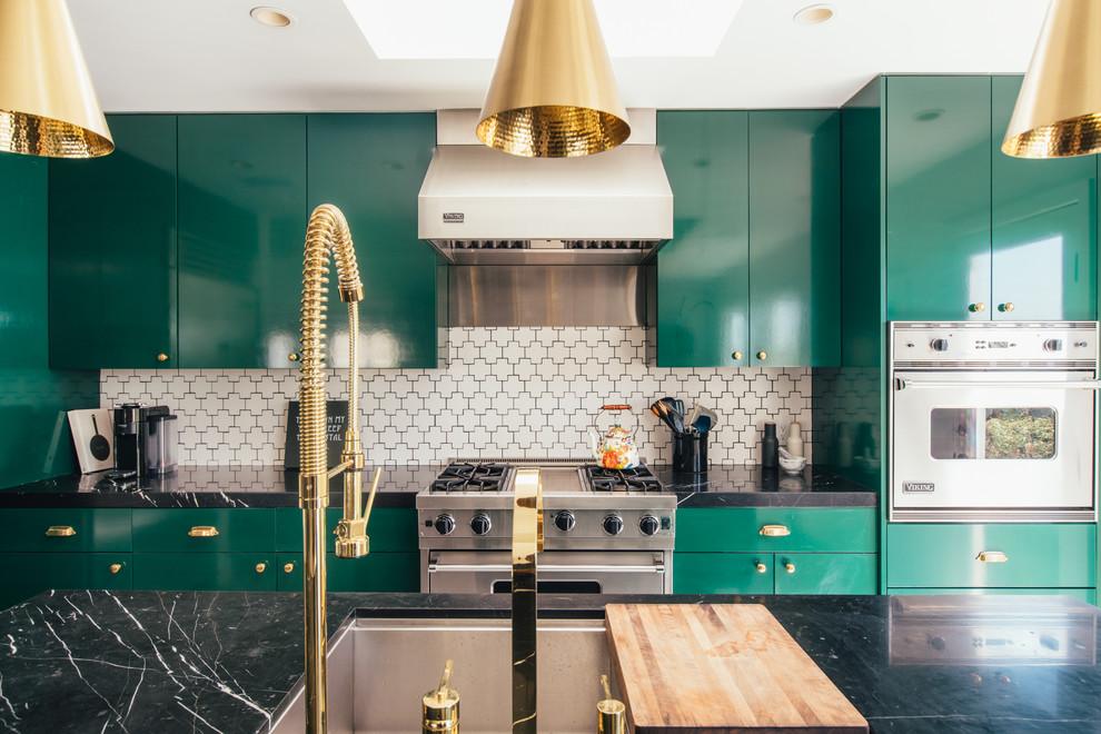 Example of a trendy galley kitchen design in Los Angeles with an undermount sink, flat-panel cabinets, green cabinets, white backsplash, stainless steel appliances, an island and black countertops