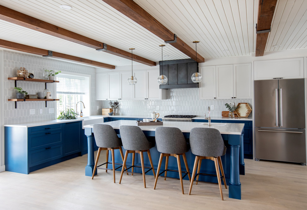 Example of a country l-shaped medium tone wood floor eat-in kitchen design in Vancouver with an undermount sink, shaker cabinets, quartzite countertops, blue backsplash, stainless steel appliances, an island and white countertops