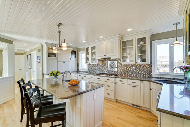 Mid-sized coastal u-shaped light wood floor and brown floor kitchen photo in New York with an undermount sink, shaker cabinets, white cabinets, multicolored backsplash, mosaic tile backsplash, stainless steel appliances and an island