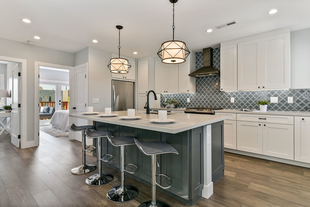 Example of a mid-sized transitional l-shaped medium tone wood floor and brown floor open concept kitchen design in San Francisco with an undermount sink, shaker cabinets, white cabinets, quartzite countertops, gray backsplash, porcelain backsplash, stainless steel appliances, an island and white countertops