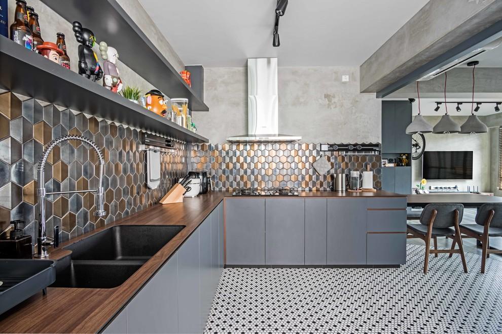 Foto de cocina en L, industrial, abierta, con fregadero de doble seno, armarios con paneles lisos, puertas de armario grises, encimera de madera, salpicadero metalizado y suelo multicolor