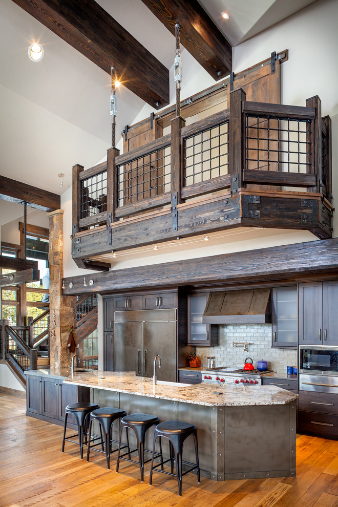 Mountain style galley medium tone wood floor open concept kitchen photo in Denver with shaker cabinets, dark wood cabinets and an island