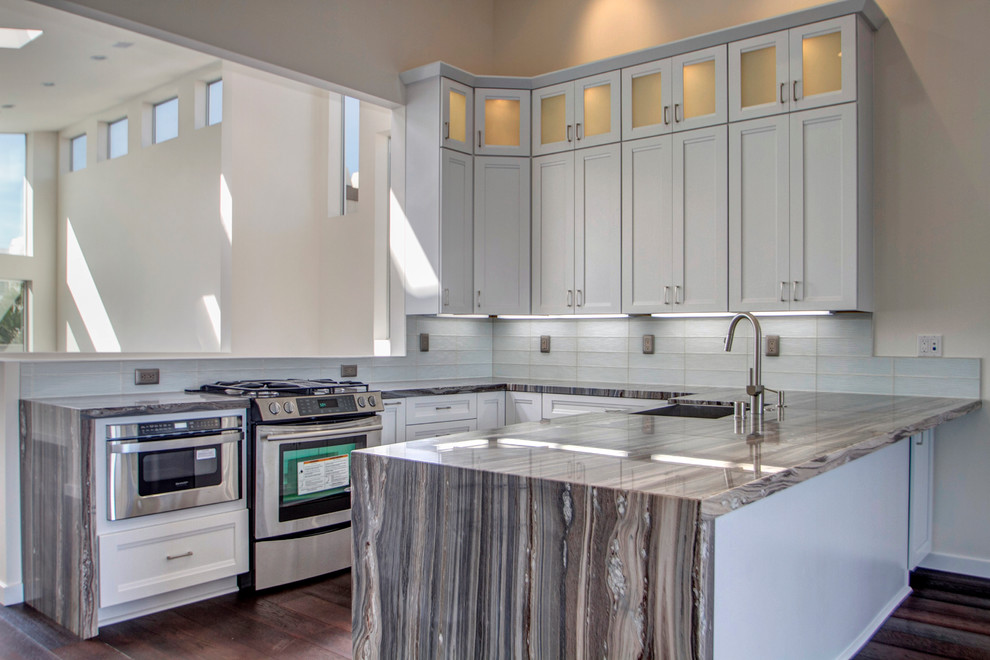 Eat-in kitchen - small transitional u-shaped medium tone wood floor eat-in kitchen idea in San Diego with a farmhouse sink, white cabinets, marble countertops, white backsplash, glass tile backsplash and stainless steel appliances