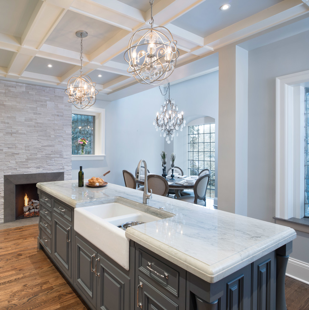 Inspiration for a mid-sized transitional l-shaped medium tone wood floor eat-in kitchen remodel in Kansas City with a farmhouse sink, raised-panel cabinets, gray cabinets, quartzite countertops, ceramic backsplash, paneled appliances and an island