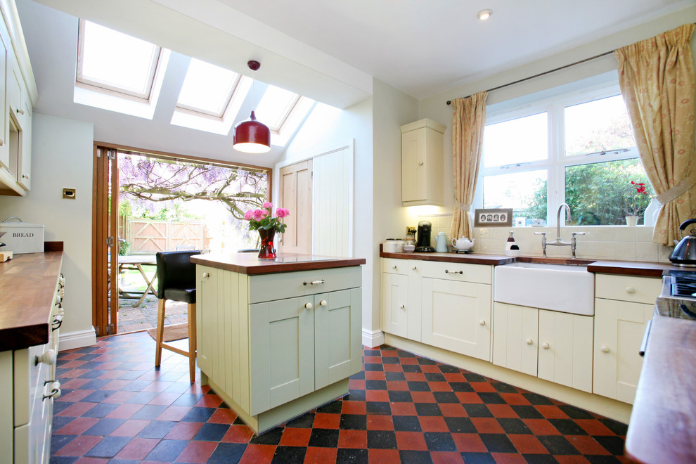 Inspiration for a timeless multicolored floor enclosed kitchen remodel in London with a farmhouse sink, yellow cabinets, wood countertops and brown countertops