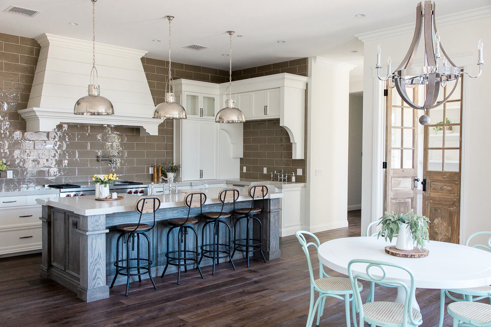 Example of a large farmhouse l-shaped dark wood floor open concept kitchen design in Phoenix with recessed-panel cabinets, white cabinets, brown backsplash, subway tile backsplash, an island, quartzite countertops and stainless steel appliances